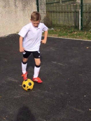 A child dribbling a football